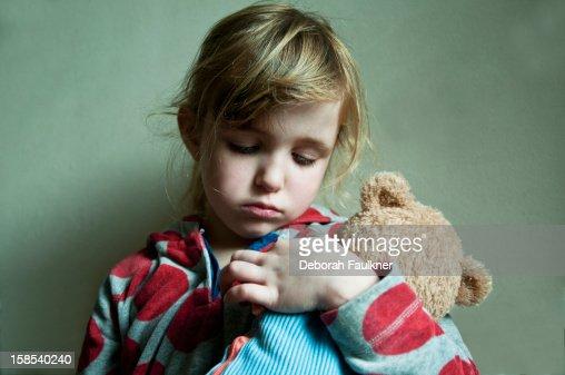 Small, sad girl cuddling a teddy : Stock Photo