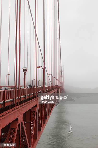 A small sailboat passes under the Golden Gate Bridge on a foggy day in San Francisco, California.