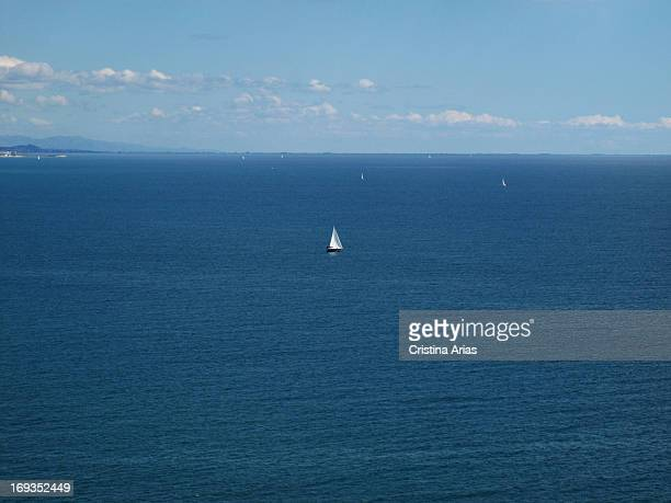Small sailing ships in a day with calm seas off the coast of Peniscola Valencian Comunity Spain April 2012