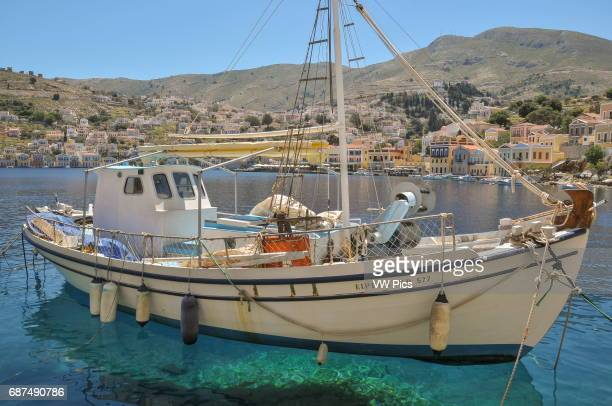 A small sailing yacht is moored along the seafront of Symi Town on the island of Symi part of the Dodecanese island chain Some of the town and its...