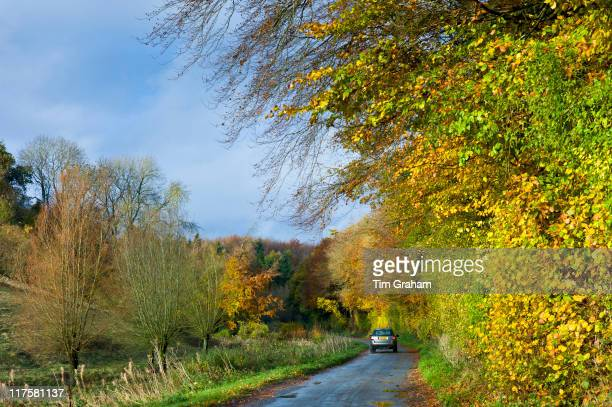 Small saloon car driven along country lane in Autumn The Cotswolds UK