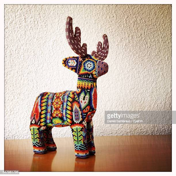 Small Sculpture Of Deer Made In Traditional Mexican Huichol On Table