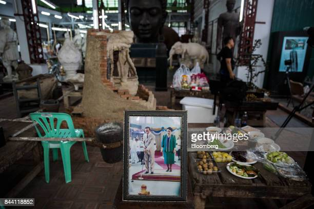 A small shrine to King Bhumibol Adulyadej sits on a table next to a photo of him and Queen Sirikit in a studio at the Fine Arts Department in Bangkok...