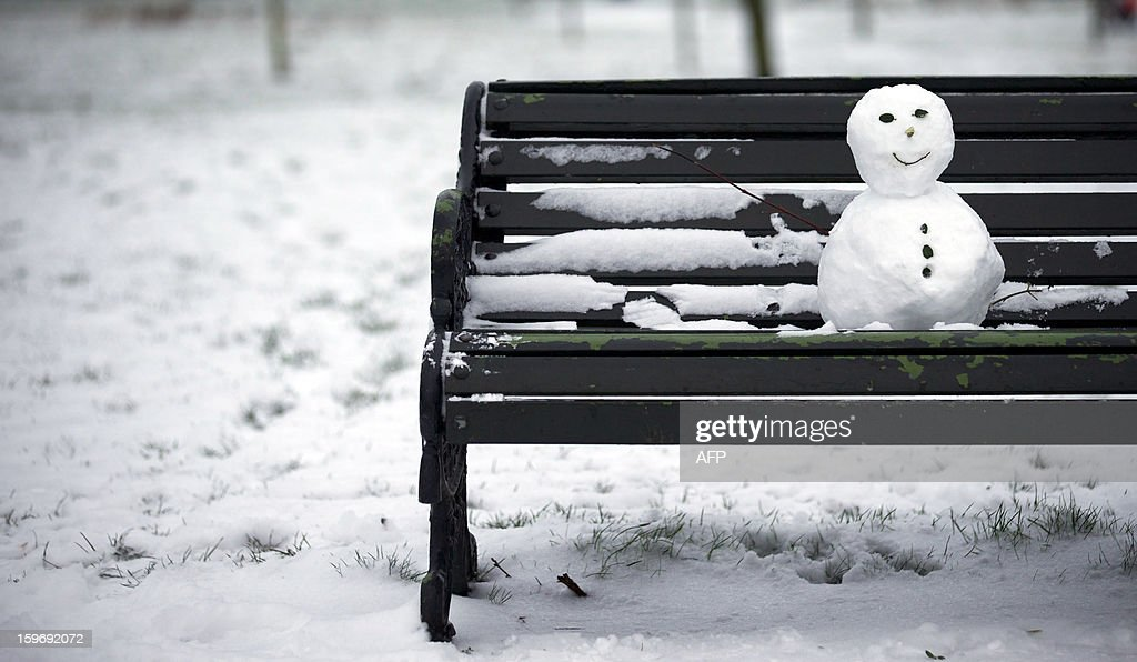 A small snow man sits on a bench in Regent's Park after snowfall in central London on January 18, 2013. Snow swept across Britain, forcing airports to cancel hundreds of flights and more than 3,000 schools to close.