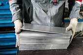 small stack of steel plates on the bench miller, hand in working glovessmall stack of steel plates on the bench miller, hand in working gloves