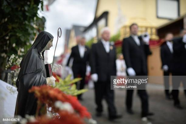 A small statue of 'Hildegard von Bingen' stands in front of a house while men carry the chest that contains the Eibingen reliquiae treasure as part...