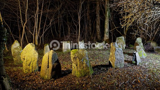 small stone circle in dark winter forest by night stock photo