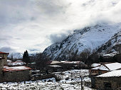 Small stone houses, buildings in the village on a beautiful mountain cold winter resort with high mountain peaks mist and snow covered rocks for snowboarding and skiing against a blue sky.