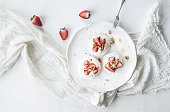Small strawberry and pistachio pavlova meringue cakes with mascarpone cream, fresh mint over white backdrop, top view