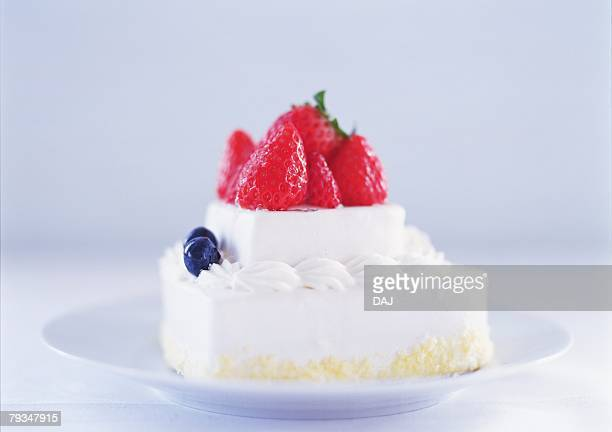 Small strawberry cake with whipped cream on plate