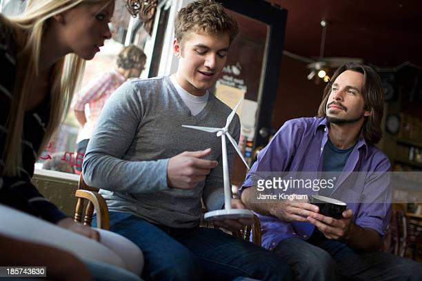 Small study group looking at model in coffee house