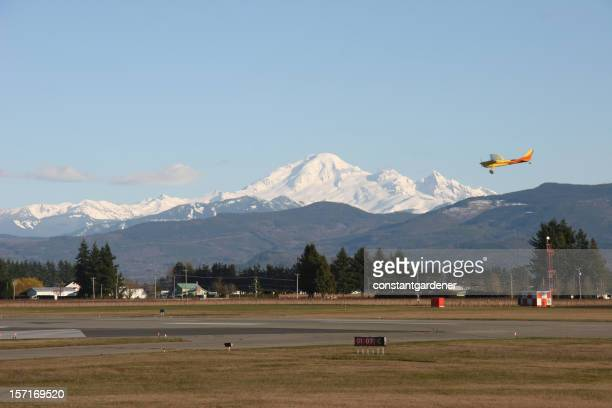 Small Town Airport with Plane and Snowcapped Mountain