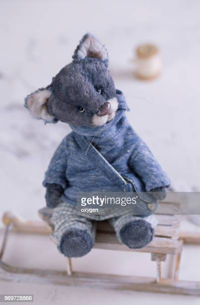 Small Toy Gray Cat in blue Sweatshirt is sitting on a sleigh