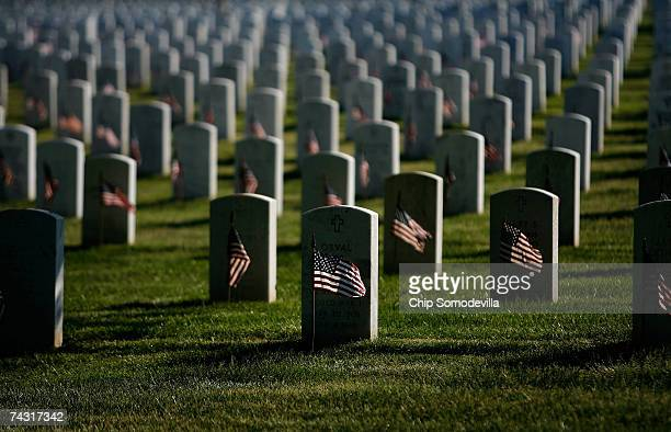 Small US flags wave in the wind after being placed in front of headstones at Arlington National Cemetery during the FlagIn Ceremony ahead of the...