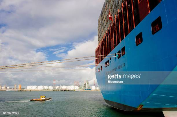 A small vessel approaches the stern of the Maersk McKinney Moeller TripleE Class ship operated by AP MoellerMaersk A/S during loading operations at...