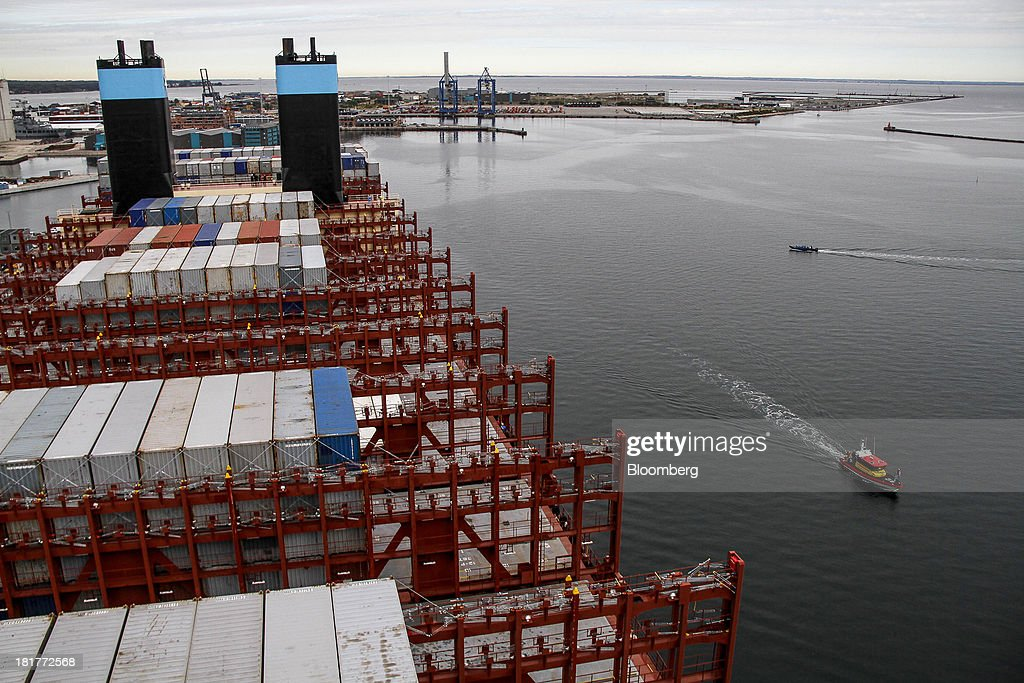 A small vessel passes shipping containers aboard the Majestic Maersk Triple E class ship, one of the world's largest vessels, operated by A.P. Moeller-Maersk A/S at Langelinie pier in Copenhagen, Denmark, on Tuesday, Sept. 24, 2013. A.P. Moeller-Maersk A/S says it won't cut its investment in developing markets from Asia to South America even as creditors turn their backs. Photographer: Freya Ingrid Morales/Bloomberg via Getty Images