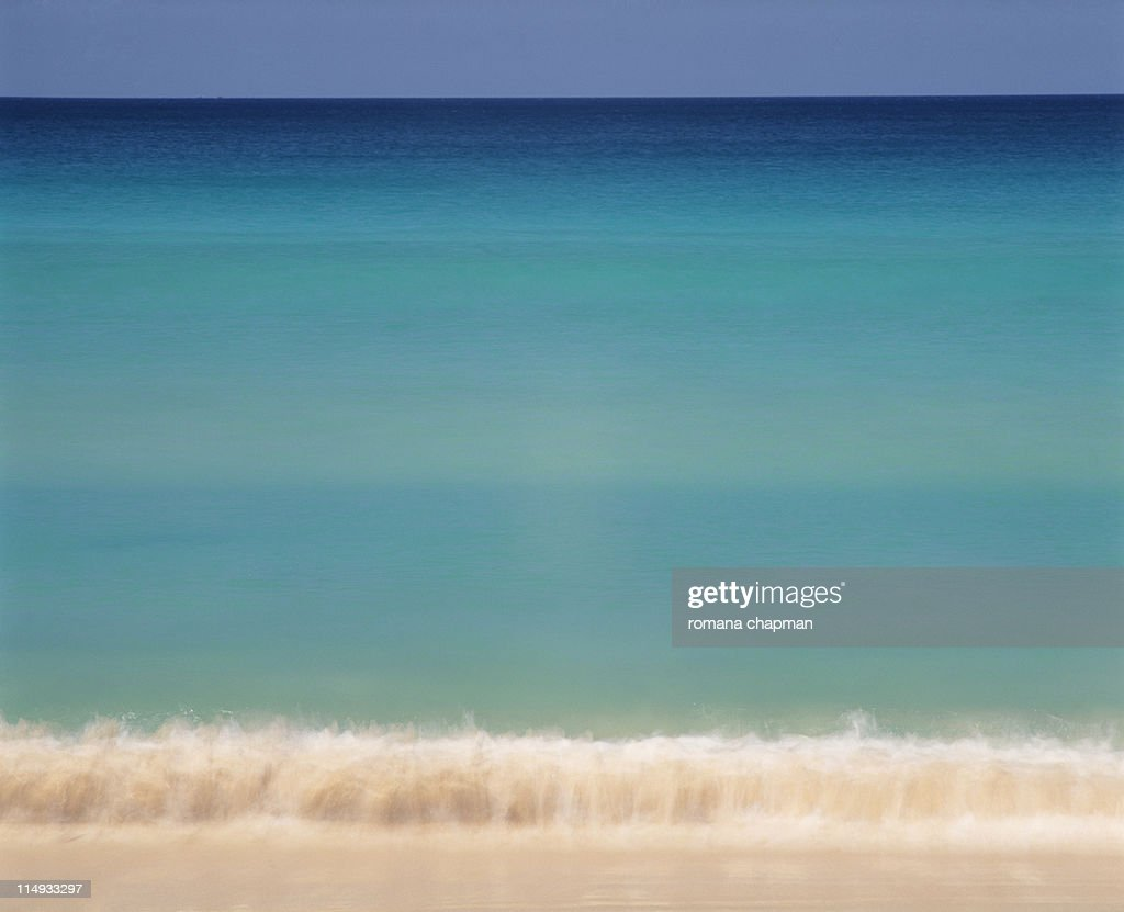 Small wave rolling onto beach from deep blue ocean