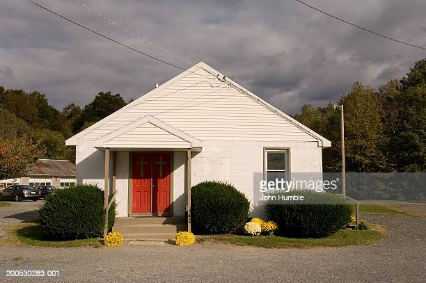Small white church with red door
