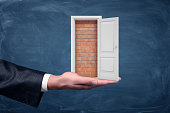 A small white door fame opening to show a brick wall that stands on a businessman's palm. Closed business. Lost opportunity. Success and failure.