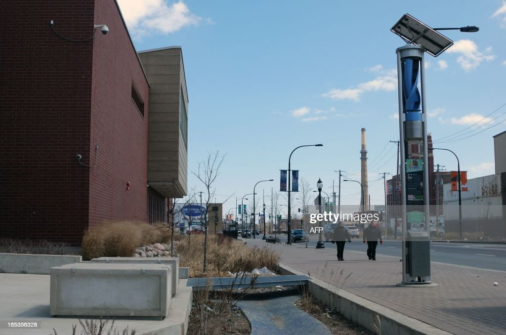 A small wind and solar generating unit used to power streetlights and a pond used to divert storm water from overtaxed sewers are seen in front of a high school on Cermak Road in Chicago, Illinois which Chicago city officials havce dubbed the greenest street in America, on April 1, 2013. The $14 million project to reshape two miles of Blue Island and Cermak also includes smog-eating pavement, sidewalks made with recycled concrete, and shrub-filled 'bioswales' to keep storm water out of overtaxed sewers.