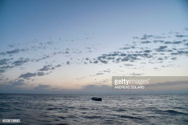 TOPSHOT A small wooden boat used by migrants to cross the Mediterranean sea is abandonned after a rescue operation of migrants by the Topaz Responder...