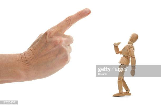 Small wooden mannequin and human hand with pointed finger