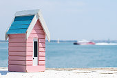 A small wooden model beach hut sat on a wall overloooking the English Channel as a boat goes by