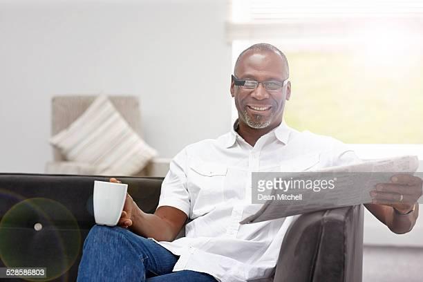 Smart afroamerikanischer Reifer Mann mit Tasse Kaffee und einer Zeitung