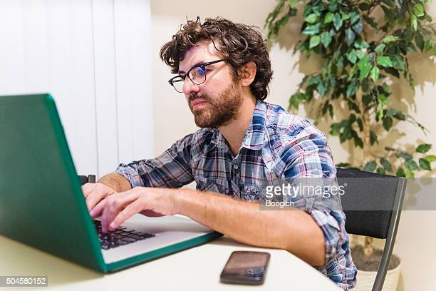 Smart American Man with Beard and Glasses Writes on Laptop