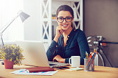Attractive young woman in eyeglasses holding hand on chin and smiling while sitting at her working place in office