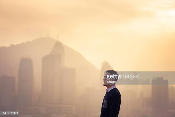 Smart businessman looking away to city skyline