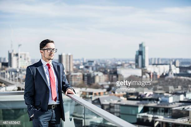 Smart businessman looking out over city