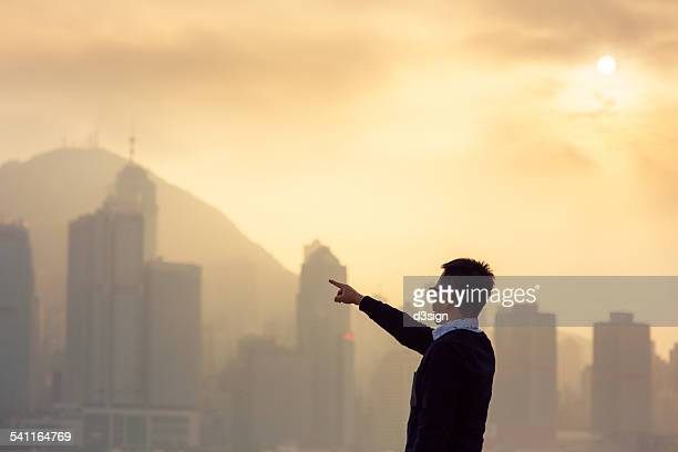 Smart businessman pointing out to the cityscape