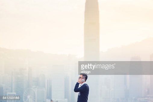 Smart businessman talking on smartphone in city : Stock Photo