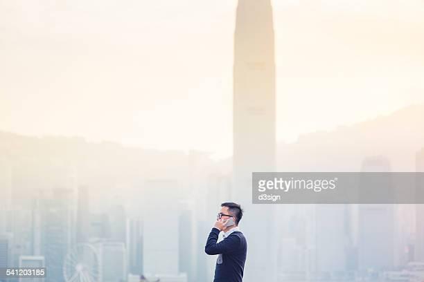 Smart businessman talking on smartphone in city