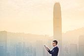 Smart businessman using digital tablet in city