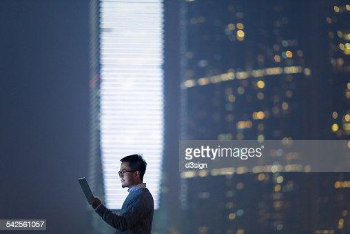 Smart businessman using digital tablet in city : Stock Photo