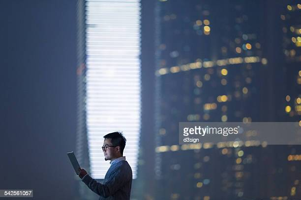 Smart businessman using digital tablet in city