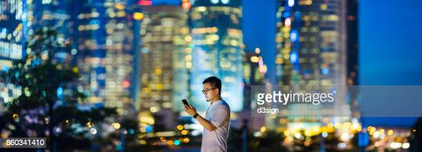 Smart businessman using smartphone against prosperous cityscape of Hong Kong at night