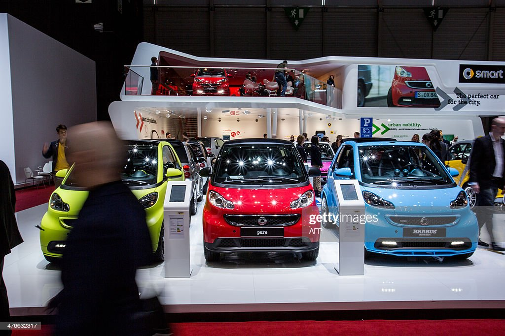 Smart cars are displayed at the group's stand of the Geneva Motor Show, on March 4, 2014. AFP PHOTO / PIERRE ALBOUY