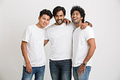 Smart Indian young male friends laughing on white background.