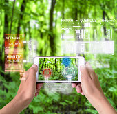 Woman using a smart device with reality augmentation graphical overlays in nature to understand the environment and plants