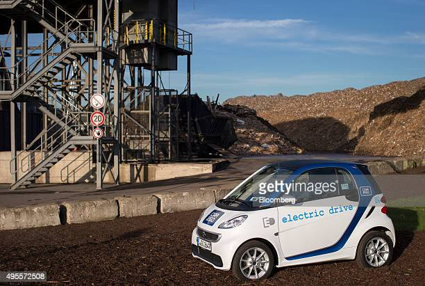 A Smart electric compact automobile produced by Daimler AG sits parked during a reusable battery storage event at the headquarters of environmental...