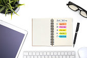 Smart goal setting with notebook, eye glasses, pen, mouse, keyboard, tablet and plant on white desk, Success concept