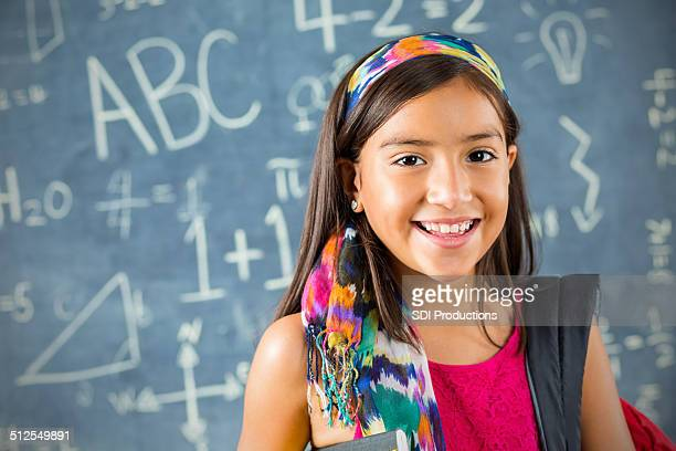 Smart Hispanic female student standing in front of class chalkboard