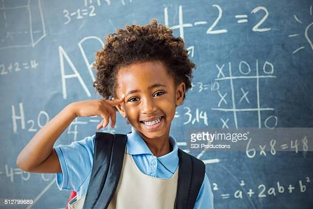 Smart asilo Studente di scuola privata che indica in testa con sicurezza