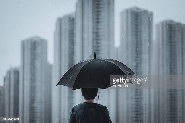 Smart male overlooking cityscape on rainy day
