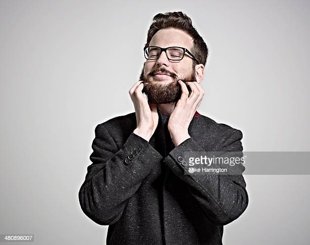 Smart man in coat and glasses scratching beard.