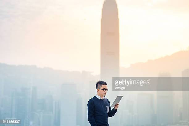 Smart man using digital tablet in urban city