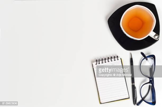 Smart office table white background with tea cup plate, eye glasses, note pad, pen with copy space